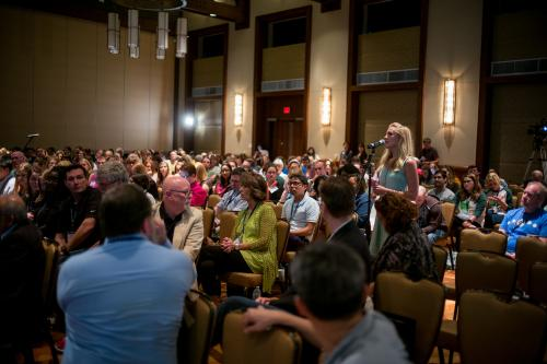 A woman asks a question into a microphone at a conference