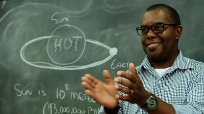 Teacher with solar system on chalkboard